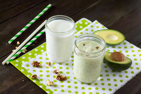 detoxification: Healthy green smoothie with walnuts and avocado with glass jar on a wooden background. Yogurt cocktail. Natural detoxification.