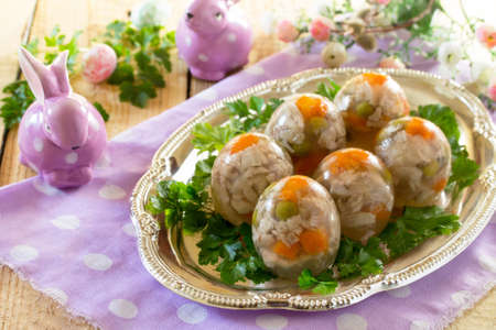 Easter treats: Easter Jellied eggs on a wooden table, jelly meat. Copy space.