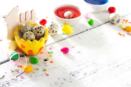 ?ooking recipe background for Easter celebration: quail eggs are, candy and twigs of willow on a white background. Festive Easter table.