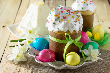 Easter background. Traditional food on the holiday table - breads with homemade raisin, cottage cheese and Easter painted eggs. Easter recipe.