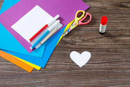 istruzione: The child makes the inscription paper items. Greeting card with paper rainbow heart. Sheets of paper, glue and scissors on a wooden table. Childrens art project, a craft for children. Craft for kids.