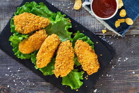 Spicy Fried Breaded chicken wings and fresh lettuce on a wooden table. 免版税图像