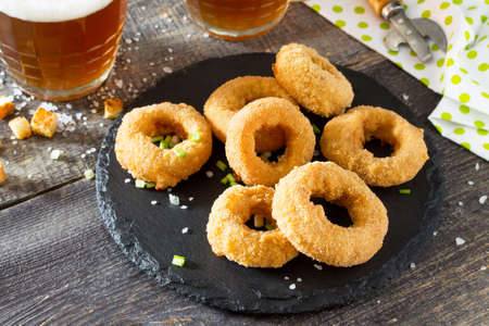 Onion rings fried with cheese on slate board. Snack food to beer on a wooden table.