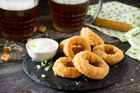 Snack food. Onion rings fried mozzarella, cheese sauce and beer glasses on a wooden table. Stock Photo