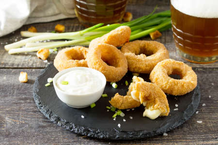 Snack food. Onion rings fried mozzarella, cheese sauce and beer glasses on a wooden table. Stockfoto