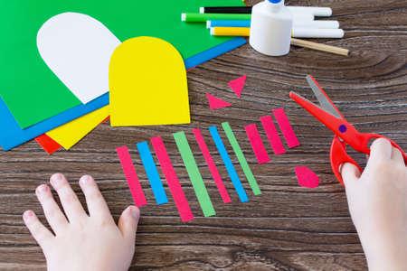 Il bambino ritaglia i dettagli di applicazione. Auguri di Pasqua galletto a mano. Progetto per bambini Arte, cucito, artigianato per i bambini. Craft per i bambini. Archivio Fotografico - 73132088