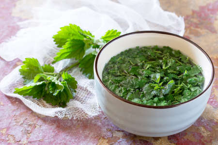 The crushed leaves brewed raw nettles on the kitchen table a rustic background.