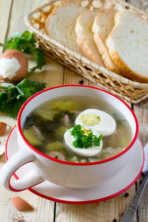 inflammatory: Soup with fresh nettles, egg, meat and potatoes. Fresh nettle leaf on the kitchen table a rustic background. Stock Photo