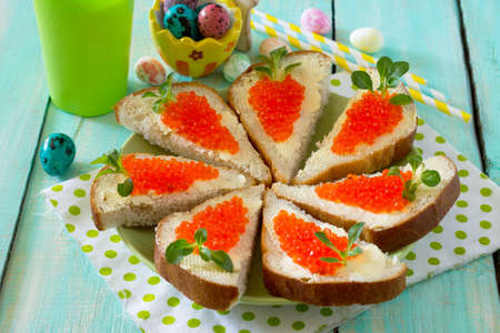 Easter carrot is a sandwich. Creative breakfast for children from bread, butter, red caviar and corn lettuce on a wooden background.