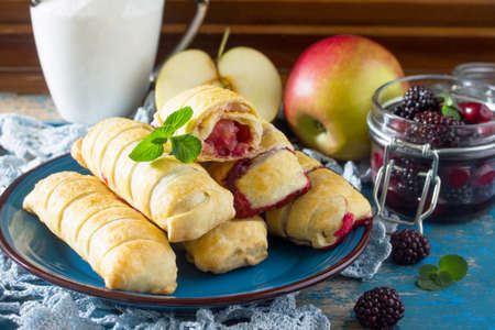 Tea and sliced home apple minischtrudel with fresh apples, cherries, blackberries and sugar powder on an antique wooden background.