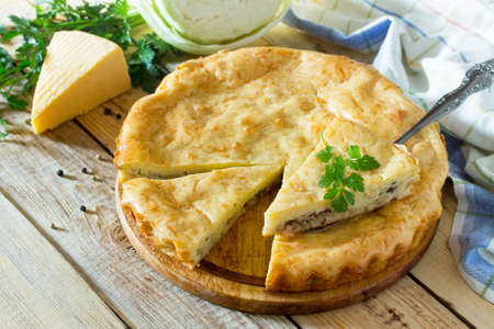 A classic quiche Lorraine pie with potatoes, cabbage, fish and cheese on a wooden table. Place for the text.