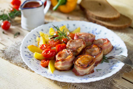 Pork fillet baked in bacon and baked potatoes, fresh vegetables and herbs on a wooden table in a rustic style. Banque d'images