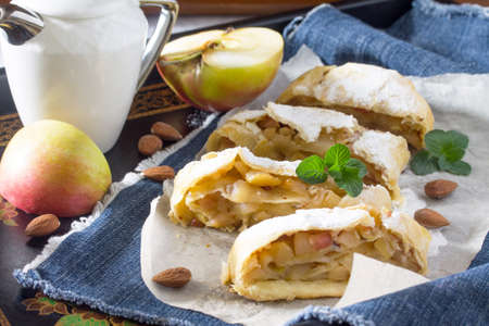 Tea and sliced homemade apple strudel with fresh apples, nuts and powdered sugar on a vintage wooden background.