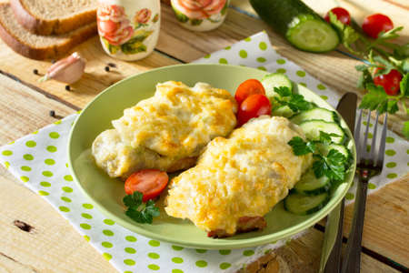 Pork steak with potatoes, grated cheese on a plate with fresh vegetables. Stock Photo
