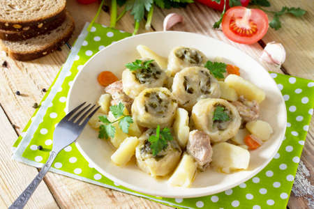Potatoes stewed with meat and rolls of dough with garlic and greens on a wooden table, served with fresh vegetables. Nudley is a national Ukrainian dish.