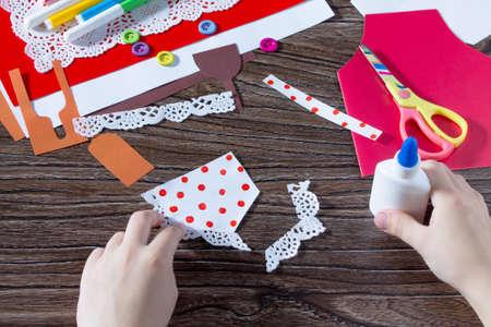 Dítě lepí papírové detaily o dárku z papírové zástěry pohlednic na den matek. Ruční. Projekt dětské kreativity, vyšívání, řemesla pro děti. Reklamní fotografie