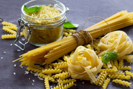 Different types of pasta with basil on the kitchen wooden table. The concept of Italian food.