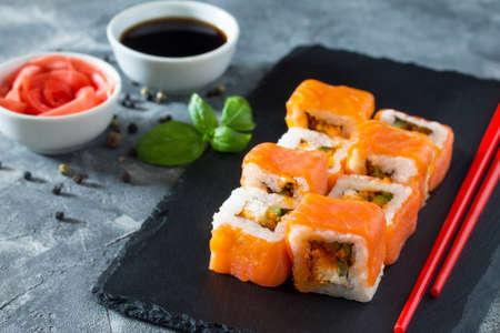 philadelphia: Roll Jamaica on a black slate board - tobiko orange salmon, salmon, soft cheese, cucumber, nori, rice. Stock Photo