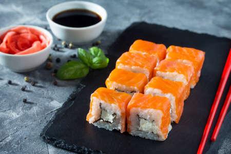 Roll Cheese salmon on a black slate board