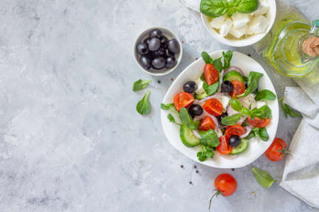 Greek salad with arugula, tomatoes, feta cheese, onions, cucumber and olives, seasoned with oil. Vitamin snack on the festive table. Top view. Stock Photo - 78966747