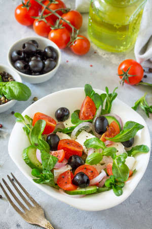 Greek salad with arugula, tomatoes, feta cheese, onions, cucumber and olives, seasoned with oil. Vitamin snack on the festive table.