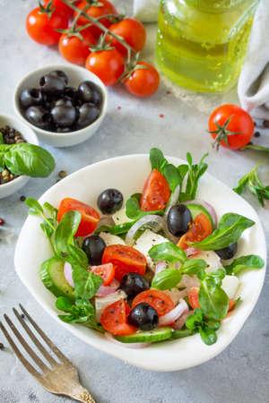 Insalata greca con rucola, pomodori, formaggio feta, cipolle, cetrioli e olive, condita con olio. Spuntino di vitamine sul tavolo festivo. Archivio Fotografico - 78912804