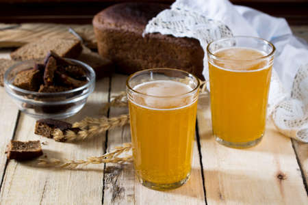 Traditional Russian cold rye drink Kvas in a glass and a jug on a wooden table. Kvass from bread, rye malt, sugar and water.
