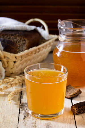 okroshka: Traditional Russian cold rye drink Kvas in a glass and a jug on the kitchen table in a rustic style. Kvass from bread, rye malt, sugar and water. Copy space. Stock Photo