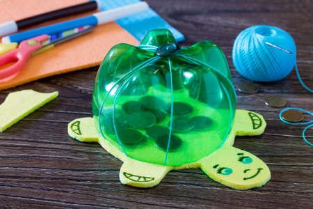 Articolo fatto a mano per bambini da una bottiglia di plastica salvadanaio per soldi. Fatto a mano. Progetto di creatività dei bambini, artigianato, artigianato per bambini. Archivio Fotografico - 80312540