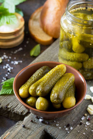 Marinated cucumbers gherkins. Pickles with mustard and garlic on a stone background.