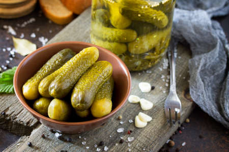 marinated gherkins: Marinated cucumbers gherkins. Pickles with mustard and garlic on a stone background.