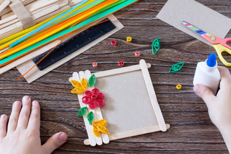 The child glues the details to a gift photo frame made of wooden sticks. Handmade. Project of children's creativity, handicrafts, crafts for children. Stock Photo - 80505580
