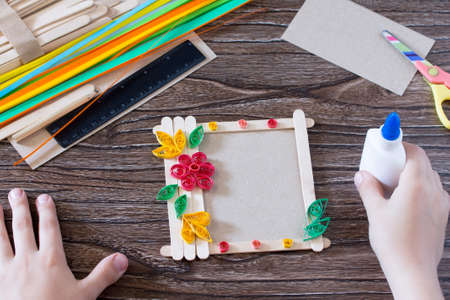 The child glues the details to a gift photo frame made of wooden sticks. Handmade. Project of children's creativity, handicrafts, crafts for children. Stock Photo - 80505581