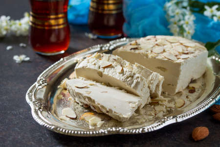 Halva with almond petals and tea on the kitchen table. Turkish and Arabic sweets. Eating Ramadan.