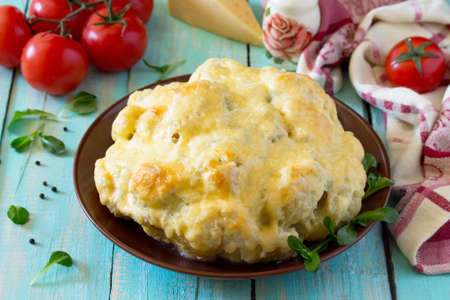 Head of cauliflower baked with cheese, stuffed with minced meat on a kitchen wooden table. Imagens