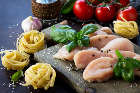 Fresh meat. Preparation of Italian cuisine pasta with chicken fillet, various spices and tomatoes on dark concrete, stone or slate. Food background.