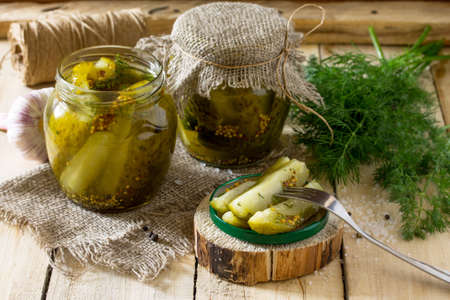 marinated gherkins: Marinated cucumbers gherkins. Marinated pickles with mustard and garlic on the kitchen table. Stock Photo