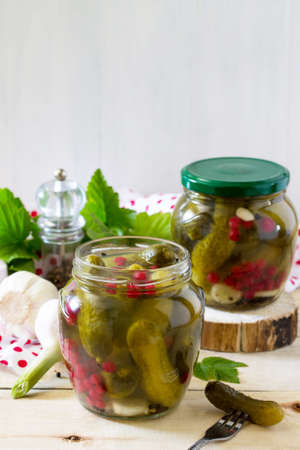 marinated gherkins: Marinated cucumbers gherkins. Marinated pickled cucumbers with red currant berries and spices on the kitchen wooden table. Stock Photo