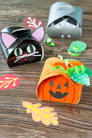 pegamento: The child creates a gift box of a black cat of Halloween, a Halloween pumpkin and a vampire box. Childrens art project, craft for children. Craft for kids.