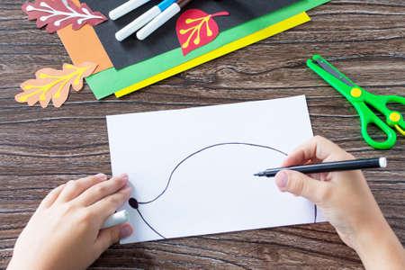 The child draws details of the application. Autumn leaf applique and hedgehog. Childrens Art Project, needlework, crafts for kids. Lizenzfreie Bilder
