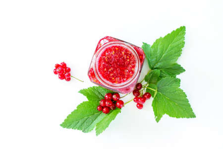 Homemade jam. Glass jar with red currant jam on white background. Preserved berry.
