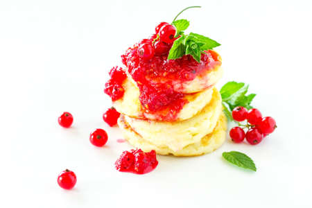 Homemade jam, red currant berries and fritters on white background. Stock Photo