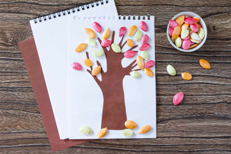 Autumn tree with colorful different leaves pumpkin seeds on a wooden background. Childrens art project, craft for children. Craft for kids.