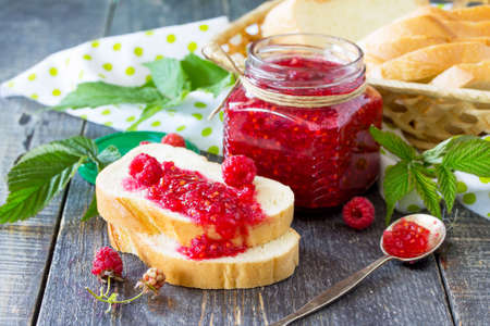 Homemade jam. Glass jar with red raspberries and white bread on the kitchen table. Preserved berry.