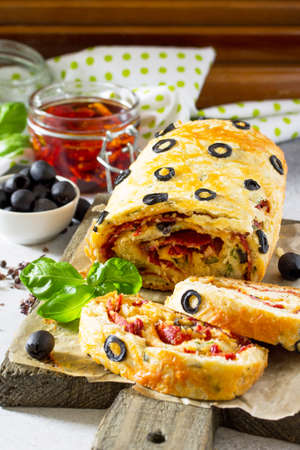 Italian cake pizza with salami, cheese, herbs, olives and sun-dried tomatoes on a stone or slate background. Italian food background. Lizenzfreie Bilder
