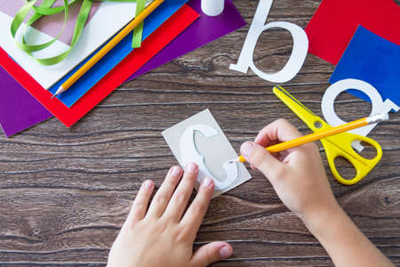 The child draws details of the application. Greeting card with a pencil and letters for the new school year. Childrens Art Project, needlework, crafts for kids.