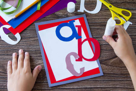 The child glues the details of the application. Greeting card with a pencil and letters for the new school year. Childrens art project, handicrafts, crafts for children.