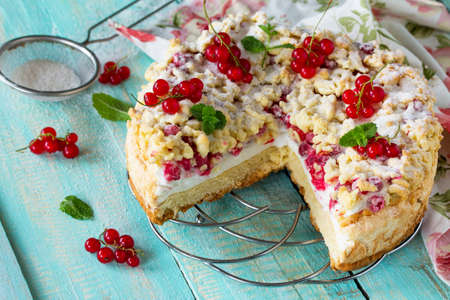 bakery products: Sweet pastries. Cupcake with Pavlov meringue and fresh summer red currants on the kitchen wooden table. Summer baking concept.