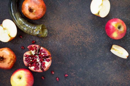 The concept of Rosh hashanah (Jewish New Year). Traditional holiday symbols - shofar, apple and pomegranate on a stone or slate table. Flat lay, top view. Lizenzfreie Bilder