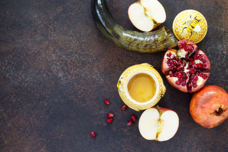 The concept of Rosh hashanah (Jewish New Year). Traditional holiday symbols - shofar, honey, apple and pomegranate on a stone or slate background. Flat lay, top view.